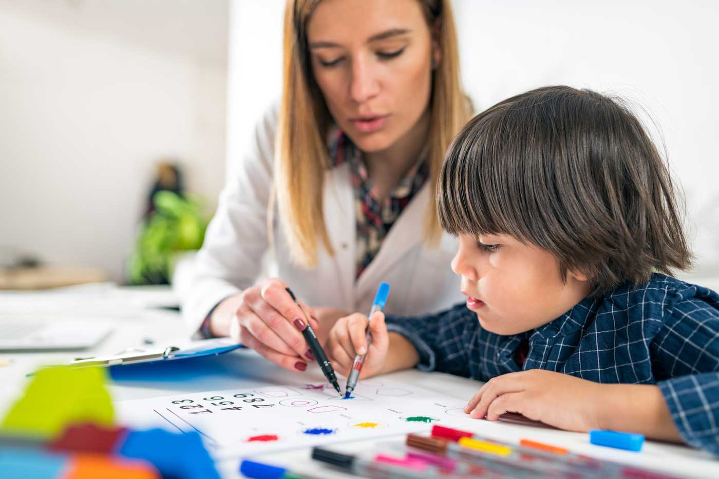 Photograph of child and therapist drawing together