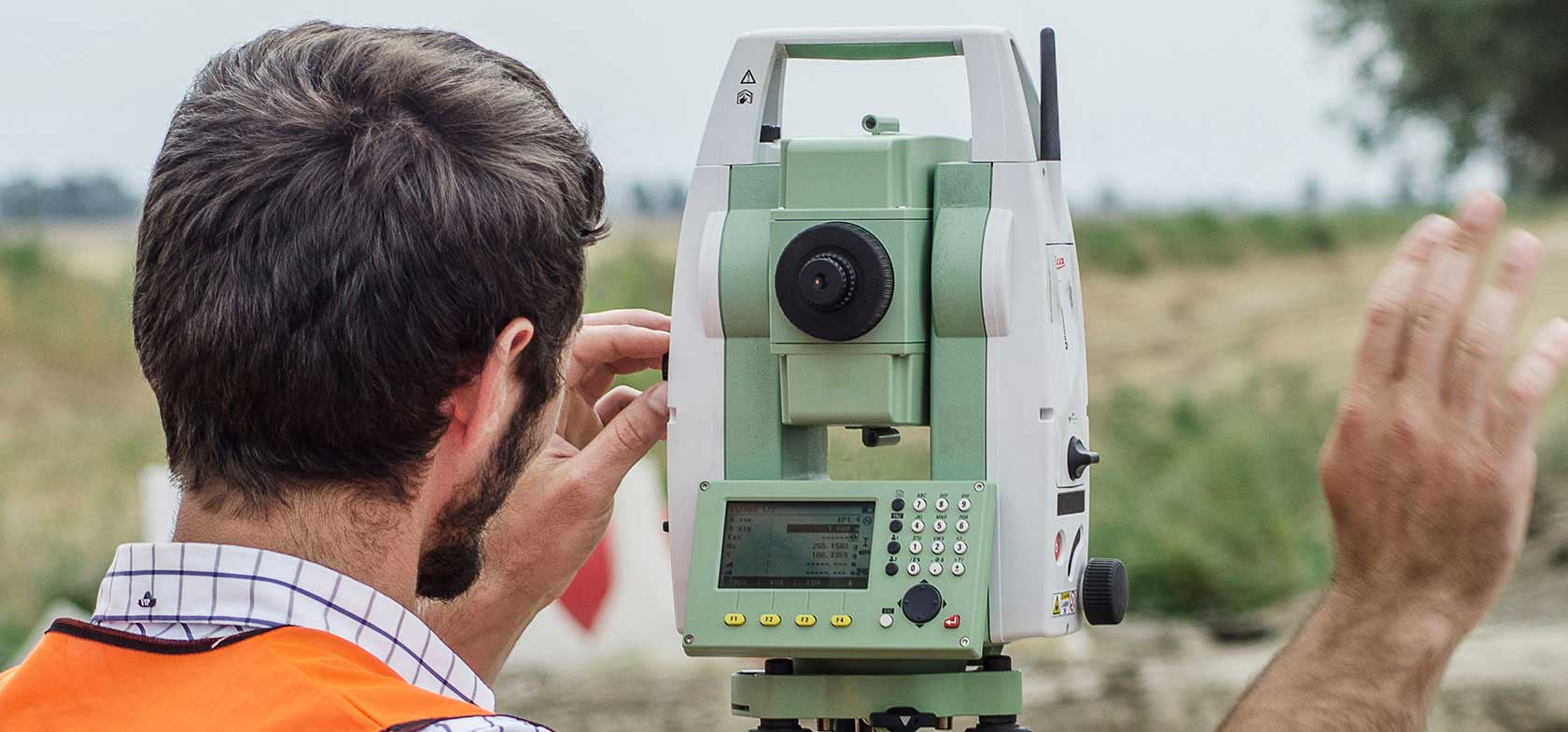 A land surveyor uses surveying equipment in the field wearing an orange safety vest