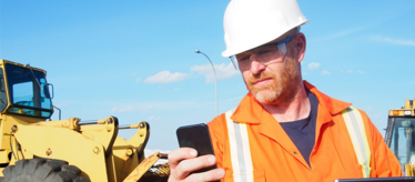 Field service technician using mobile form while wearing safety gear