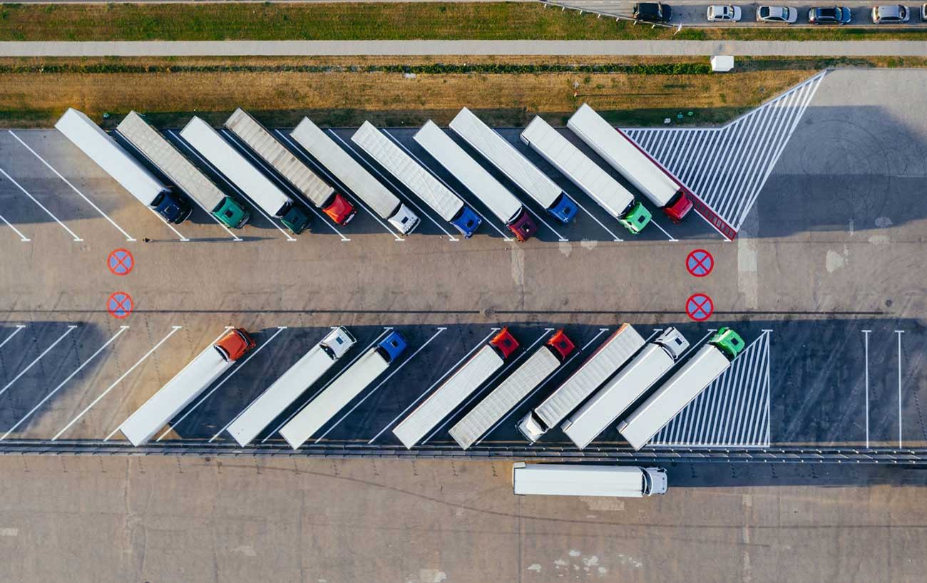 Aerial view of numerous transport trucks parked in parking lot